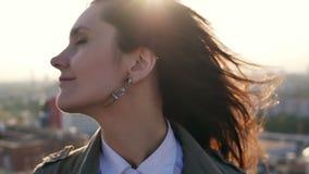 特写镜头 站立在屋顶的少妇在日落转动看照相机的头和她的头发 缓慢的mo 股票录像