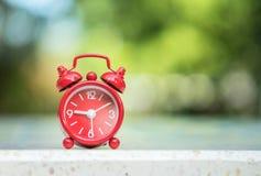 特写镜头红色闹钟显示七个小时和十五分钟在屏幕上在被弄脏的大理石书桌和公园视图背景 免版税库存照片