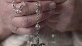 特写镜头耶稣受难象,水晶念珠在老手上 影视素材