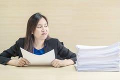 特写镜头职业妇女从堆在她前面的工作证明书烦人在被弄脏的木书桌和木墙壁te上的工作概念 免版税库存图片