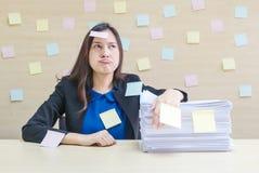 特写镜头职业妇女从堆坚苦工作和工作证明书烦人在她前面在工作概念在被弄脏的木书桌上和 库存图片