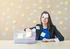 特写镜头职业妇女从堆坚苦工作和工作证明书烦人在她前面在工作概念在被弄脏的木书桌上和 图库摄影