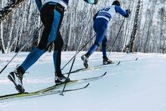 特写镜头脚短跑经典样式的两个滑雪者在冬天森林里 免版税库存图片