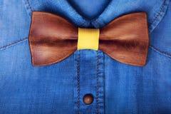 特写镜头舱内甲板放置有木黄色蝶形领结的人的偶然蓝色牛仔裤衬衣 人辅助部件 另外的背景企业格式 免版税库存图片