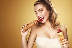 特写镜头表面纵向妇女 获得美丽的白肤金发的少妇吃法国热狗的乐趣慕尼黑啤酒节假日 免版税图库摄影