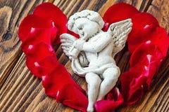 特写镜头观点的与喇叭的美丽的丘比特,在红色玫瑰花瓣附近的天使装饰小雕象在木背景 免版税库存图片