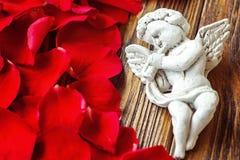 特写镜头观点的与喇叭的美丽的丘比特,在红色玫瑰花瓣附近的天使装饰小雕象在木背景 免版税图库摄影
