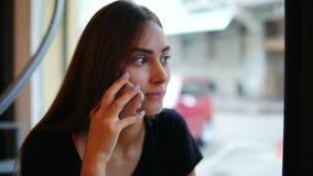 特写镜头观点的可爱的少妇谈话在坐由在咖啡馆的窗口的咖啡馆的电话 股票视频