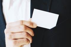 特写镜头观点的商人去掉从他的夹克口袋的一张空白的白色名片 水平的大模型,被弄脏 图库摄影