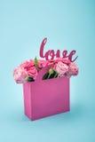 特写镜头观点的在纸箱和爱标志的美丽的开花的桃红色玫瑰 免版税库存图片