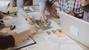 特写镜头观点的工作在桌上的混合的族种人 谈论的队建筑设计,新运作公司 免版税库存图片