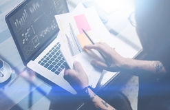 特写镜头观点的成人刺字了工友与膝上型计算机一起使用在工作场所 商人分析在手上的文件 图形 免版税库存图片
