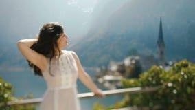 特写镜头观点的排序她的头发的葡萄酒礼服的女孩在老河镇的背景的 股票视频