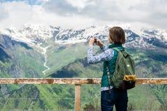 特写镜头观点的有拍照片和享受山景的智能手机的年轻女性游人 库存照片