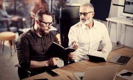 特写镜头观点的群策群力过程的商人 做在笔记本的有胡子的成人人笔记 工友配合 免版税库存照片