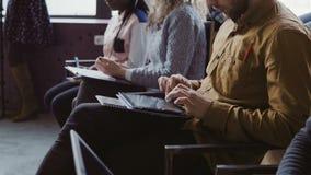 特写镜头观点的年轻多种族队坐在业务会议上 男人和妇女在片剂和笔记本做笔记 股票录像
