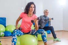 特写镜头视图适合年轻深色女性行使与哑铃坐瑞士球在小组健身类期间 免版税库存图片
