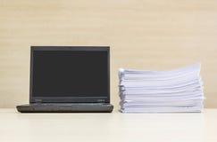 特写镜头黑计算机笔记本和堆在被弄脏的木书桌和木头墙壁上的工作证明书在会议室纹理背景, bea中 库存图片