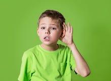 特写镜头画象儿童听力某事,父母谈话,闲话,在绿色背景对耳朵姿态的手隔绝的 免版税库存照片