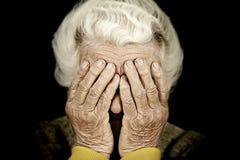 特写镜头画象压下了盖她的面孔的老妇人用手 免版税图库摄影