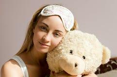 特写镜头画象拥抱有蓝眼睛&睡眠绷带的玩具熊美丽的白肤金发的少妇在她的头&愉快微笑 免版税库存图片