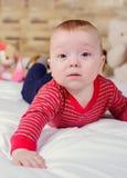 特写镜头画象观点的有说谎在与今后看软的毯子的床上的金发的一个滑稽的微笑的逗人喜爱的矮小的男婴 免版税库存照片