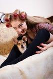 特写镜头画象逗人喜爱的小狗&美丽的白肤金发的年轻画报妇女有蓝眼睛的有乐趣放松的说谎在床 库存图片