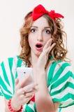 特写镜头画象震惊举行的流动手机画报女孩美丽白肤金发与有红色丝带的蓝眼睛小姐 免版税库存照片