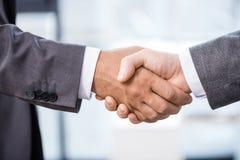 特写镜头部份观点的在握手的礼服的两个商人 免版税库存照片
