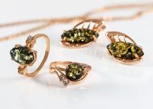 特写镜头金黄圆环和耳环有地道自然波儿地克的绿色琥珀的丙烯酸酯的表面上 免版税库存图片