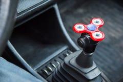 特写镜头锭床工人坐立不安是转轨的时间的一个玩具在站立的汽车在汽车交通堵塞 图库摄影