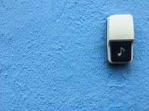 特写镜头门铃按钮有蓝色背景 免版税库存图片