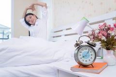 特写镜头闹钟有与一名愉快的妇女的一好天儿在床在醒以后在醒以后 库存照片