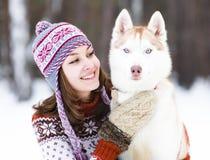 特写镜头青少年女孩拥抱逗人喜爱的狗在冬天公园 免版税图库摄影