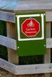 特写镜头骑自行车者卸下在篱芭的标志 库存照片