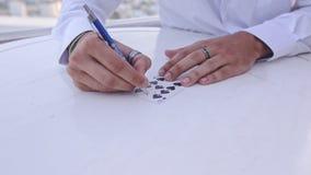 特写镜头魔术师手指示与笔的树荫卡片在白色表上 股票视频