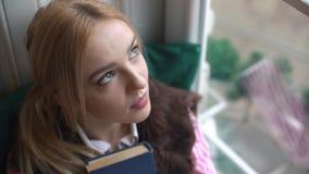 特写镜头,一个美丽的女孩的画象有看窗口和入照相机的书的 影视素材