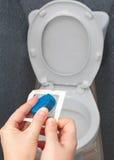 特写镜头,手打开洗手间坦克的蓝色清洁片剂 库存照片
