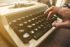 特写镜头,键入在一台老打字机的手 图库摄影