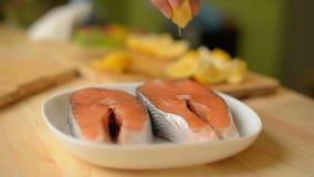 特写镜头A女孩通过洒一块鲑鱼排紧压柠檬在油煎它前 影视素材