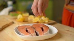 特写镜头A女孩通过洒一块鲑鱼排紧压柠檬在油煎它前 股票录像