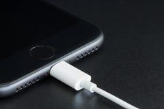 特写镜头iPhone 7表面无光泽的黑色连接到usb缆绳 免版税库存图片