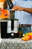 特写镜头man& x27; 使用汁液制造商的s手,插入苹果片入机器,健康生活方式概念 库存图片