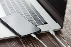 特写镜头usb缆绳连接电话和便携式计算机新的technol 免版税库存图片