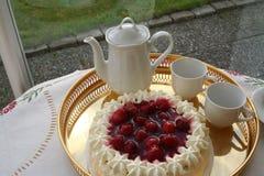 特制的糕饼用草莓和奶油等待与一个杯子浓咖啡一起供食 免版税库存图片