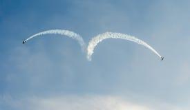 特技飞机驾驶在布加勒斯特市的天空的训练,罗马尼亚 有踪影烟的色的飞机 免版税库存照片