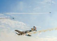 特技飞机驾驶在布加勒斯特市的天空的训练,罗马尼亚 有踪影烟的色的飞机 免版税库存图片