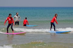 特拉唯夫,以色列- 04/05/2017 :女孩沿在地中海的波浪赛跑 冲浪为孩子的学校 库存图片