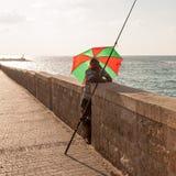 特拉维夫,以色列- 2011年9月9日:成人人钓鱼在特拉维夫散步的伞下 免版税库存照片