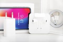 特拉维夫,以色列- 2017年11月23日:有充电器和耳机的Iphone x巧妙的电话 最新苹果计算机Iphone 10手机 库存照片